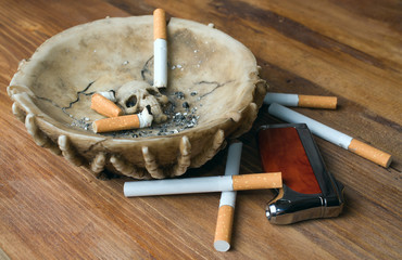 ashtray, lighter and cigarette on a wooden table