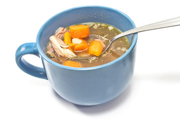 Beef and vegetable broth in  bowl with spoon on white