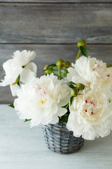 White peonies in a wicker vase