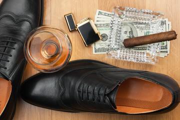 Cigar, ashtray, lighter, money, shoe, glass   on  wooden floor