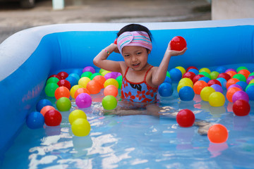 Little girl playing ball in the kiddie pool.