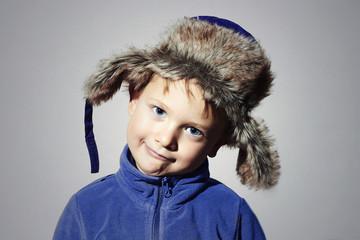funny child in fur Hat.winter little boy in blue sport sweater