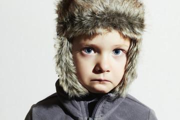 Sad child in fur Hat.winter little boy.children emotion
