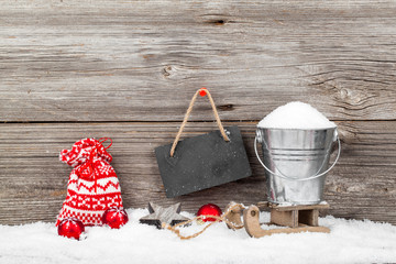 Snow in a bucket on a sled, on wooden background, with Christmas