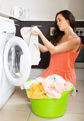 Unhappy  girl using washing machine at home