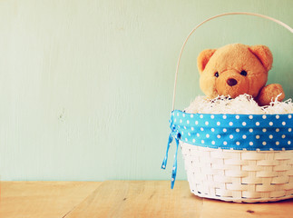 toy teddy bear in basket on wooden table. retro filtered image