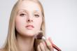canvas print picture - Junge Frau pudert sich das Gesicht