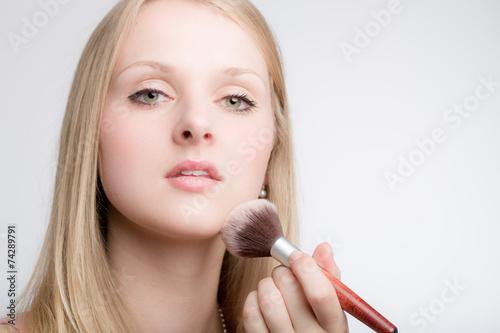 canvas print picture Junge Frau pudert sich das Gesicht