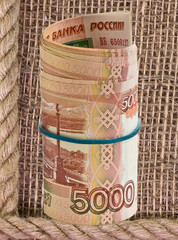 Russian rubles rolled into a tube on a background of burlap