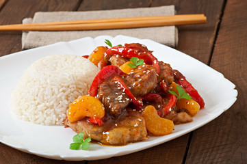 Meat in a spicy sauce, sweet pepper and tangerines with a garnis