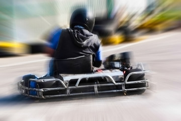 A man is driving Go-kart with speed in the park.