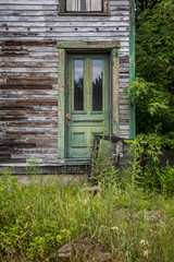 Green exterior door on neglected abandoned house