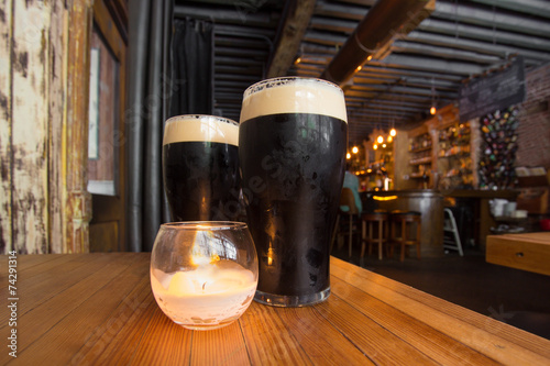 Aluminium Bier Dark beer and candle in pub setting