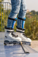 Teen with roller skates ready for a stunt on a half pipe ramp