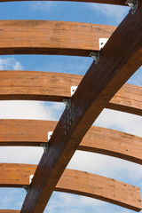 Timber frame arch against blue sky midday underneath view.