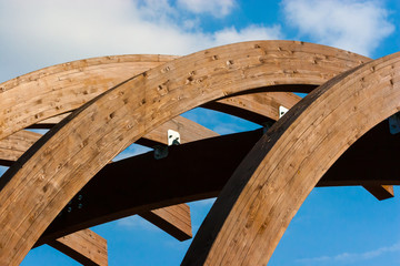Timber frame arch against blue sky midday.