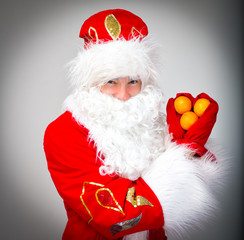Santa Claus shows heart made of tangerines.
