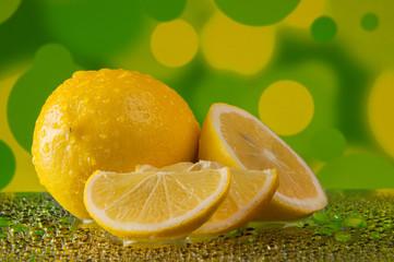 Lemons in water drops on on mottled yellow-green background