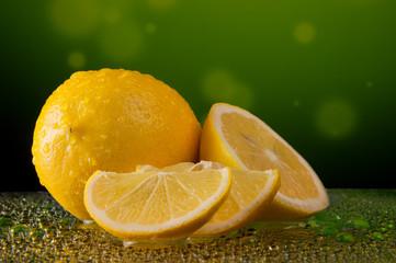 Lemons in water drops on mottled green background