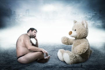 Strange naked man looks at toy bear