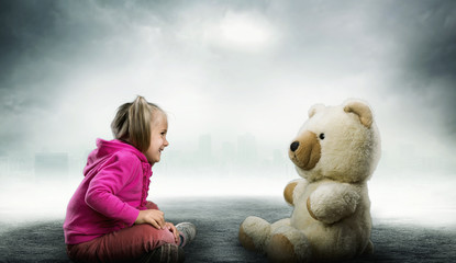 Small cute girl sits and looks at toy bear