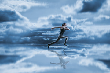 Woman running against blue sky