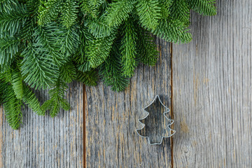 Tree branch on rustic wooden background  with cookie cutter orna