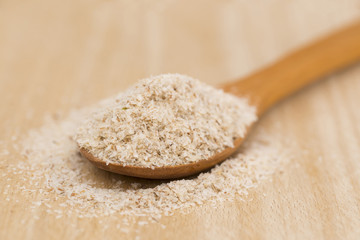 Wooden Spoon with Psyllium Seeds on wooden background