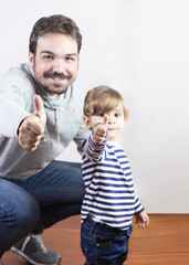 Father and her little daughter with thumbs up