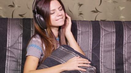 Girl with headphones on sofa