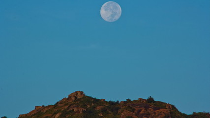 large moon sets over the mountain