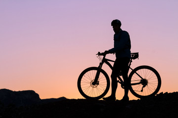 Silhouette of a cyclist with sunset on the top of a hill