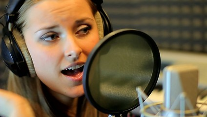 Teen girl sing at the professional audio studio. Portrait view