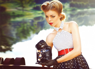 beautiful retro girl in vintage clothing with vintage camera in