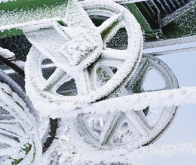 Frozen metal wheel covered in ice and snow