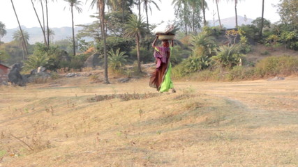 Indian rural woman carries heavy things on her head