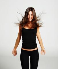 Beautiful girl in black leggings and a t-shirt, tossed hair, smi