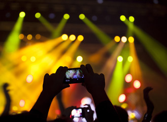 People enjoying rock concert and taking photos with cell phone a