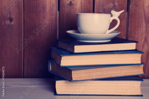 Old books and cup of coffee on table - 74304573