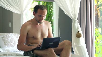 Young handsome man with laptop computer relaxing on bed