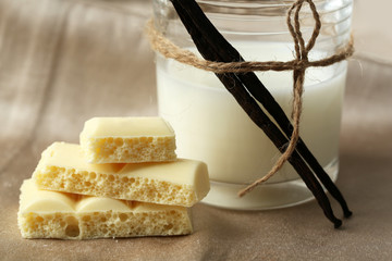 Tasty white porous chocolate with vanilla sticks and glass of