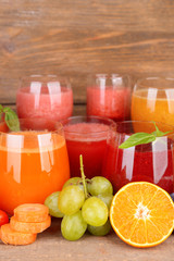 Glasses of tasty fresh juice, on wooden table.