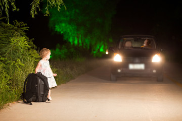 Little girl hitchhiker on the side of road at night