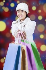 Cheerful girl giving shopping bags