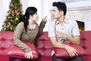 Couple quarreling on sofa in christmas day