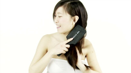 Happy Chinese woman brushing long silky hair medium shot