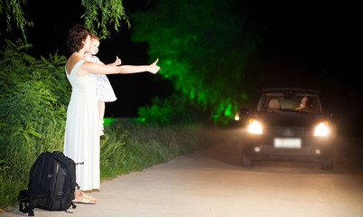 Mom with daughter hitchhiker on the side of road at night