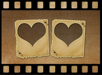 Old paper slides in the form of hearts on abstract grunge backgr