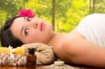 beautiful brunette woman lying down in outdoor spa