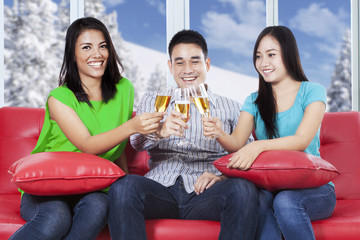Happy people drinking champagne on couch